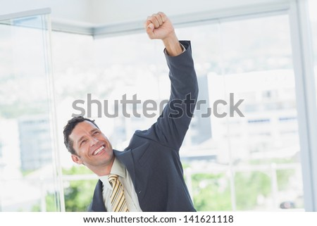 Cheerful businessman raising up his hand in office