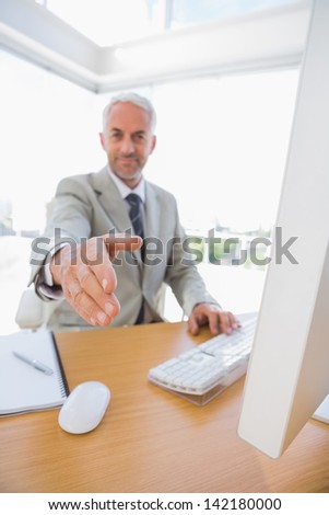 Cheerful businessman reaching hand out for handshake at his desk