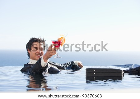Cheerful businessman relaxing in a swimming pool with a cocktail in a suit - stock photo