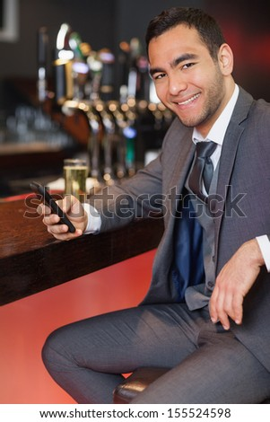 Cheerful businessman sending a text while having a drink in a classy bar - stock photo