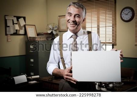 Cheerful businessman showing a blank sign and smiling, 1950s office on background. - stock photo