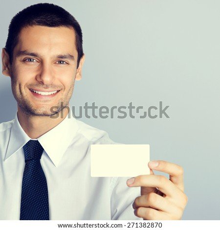 Cheerful businessman showing blank business or plastic credit card, with copyspace area for text or slogan, specially toned - stock photo