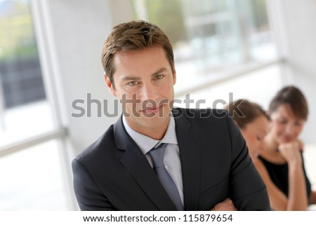 Cheerful businessman sitting in front of colleagues - stock photo