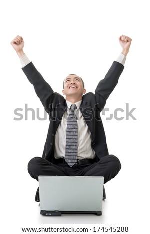 Cheerful businessman sitting on ground and raising hand, full length portrait. - stock photo