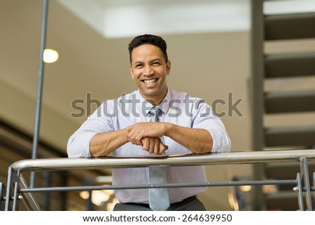 cheerful businessman standing by stairway - stock photo