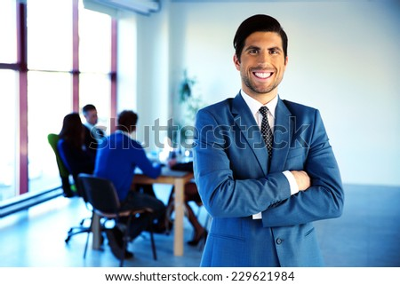 Cheerful businessman standing with arms folded in front of colleagues - stock photo