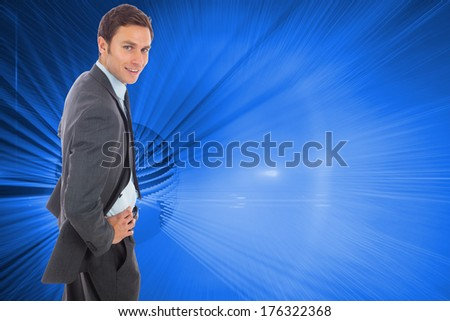 Cheerful businessman standing with hands on hips against global technology background