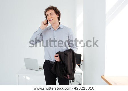 Cheerful businessman talking on the phone in office - stock photo