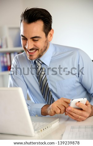 Cheerful businessman using mobile phone - stock photo