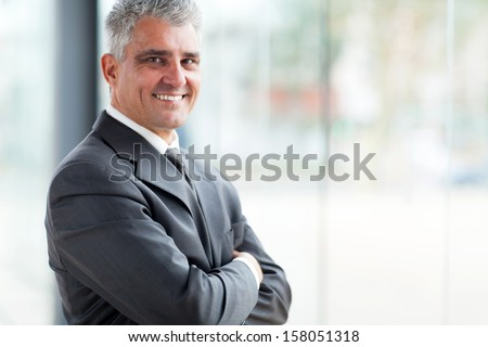 cheerful businessman with arms folded looking at the camera - stock photo