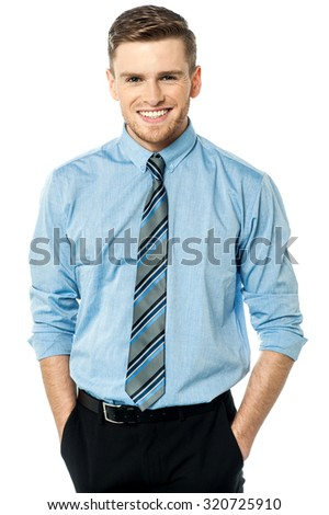 Cheerful businessman with hands in pocket - stock photo