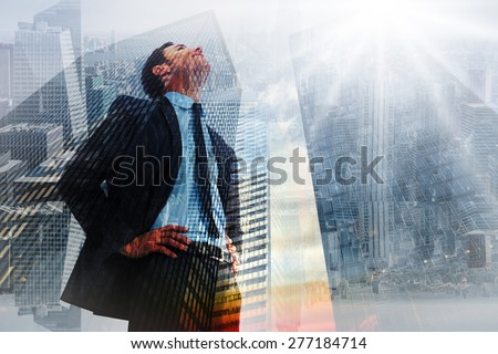 Cheerful businessman with hands on hips against low angle view of skyscrapers at sunset - stock photo