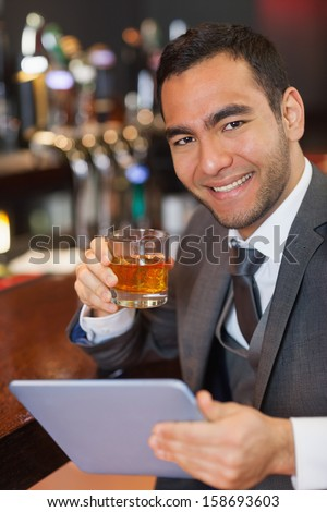 Cheerful businessman working on his tablet while having a whiskey in a classy bar