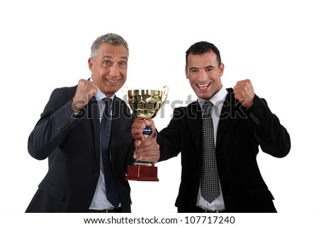 cheerful businessmen holding a golden cup - stock photo