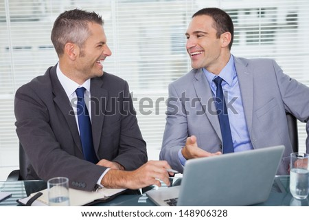 Cheerful businessmen laughing while working in bright office - stock photo