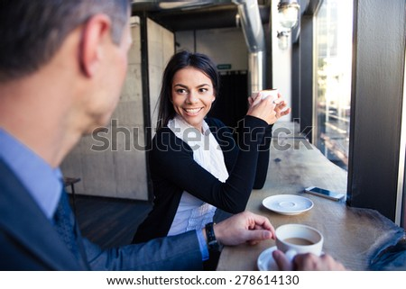 Cheerful businesswoman and businessman drinking coffee in cafe  - stock photo