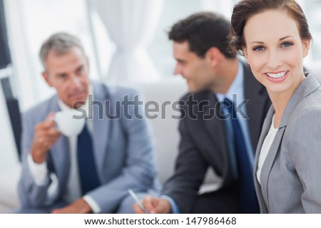 Cheerful businesswoman having a meeting with her colleagues in bright office