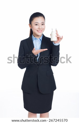 cheerful businesswoman holding a bottle of milk against white background - stock photo