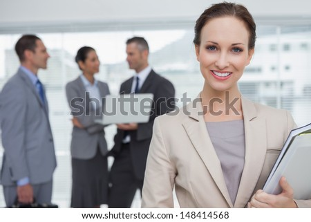 Cheerful businesswoman holding files smiling at camera in bright office