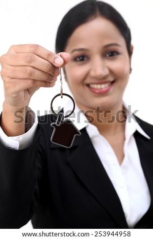 Cheerful businesswoman holding house key - stock photo