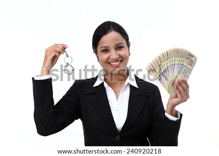 Cheerful businesswoman holding house key and currency notes - stock photo