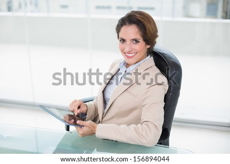Cheerful businesswoman holding tablet in bright office - stock photo