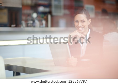 Cheerful businesswoman on a coffee break looking out the window