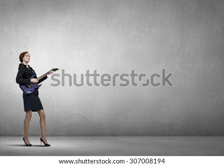 Cheerful businesswoman playing electric guitar on cement background - stock photo