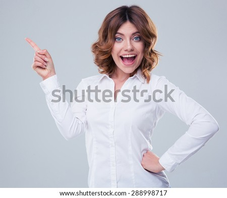 Cheerful businesswoman pointing finger away over gray background