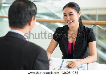Cheerful businesswoman providing a male entrepreneur with consulting services - stock photo