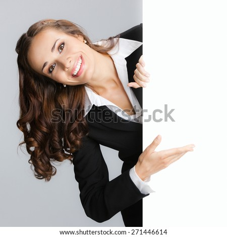 Cheerful businesswoman showing signboard with blank copyspace area for text or slogan - stock photo