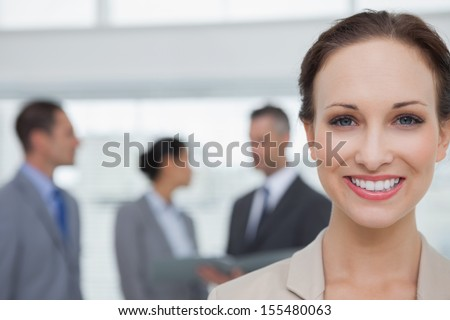 Cheerful businesswoman smiling at camera in bright office