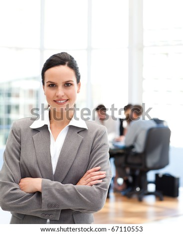 Cheerful businesswoman standing in front of her team while working in the background