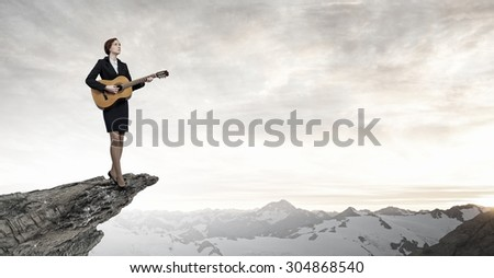 Cheerful businesswoman standing on rock edge and playing acoustic guitar