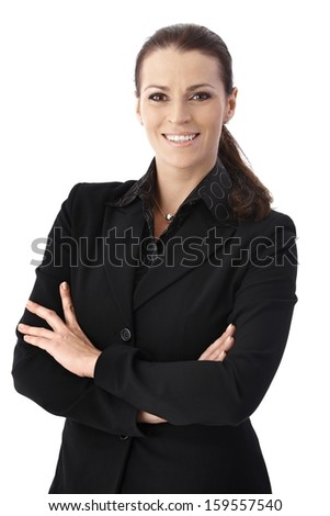 Cheerful businesswoman standing with arms folded, smiling at camera. - stock photo
