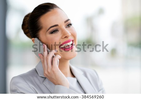 cheerful businesswoman talking on cell phone - stock photo
