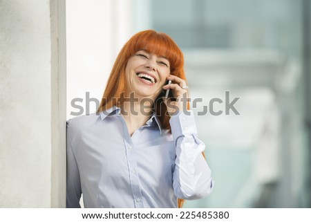 Cheerful businesswoman talking on cell phone in office - stock photo