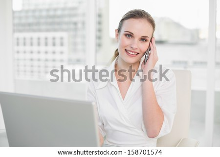 Cheerful businesswoman using laptop and making a call in her office