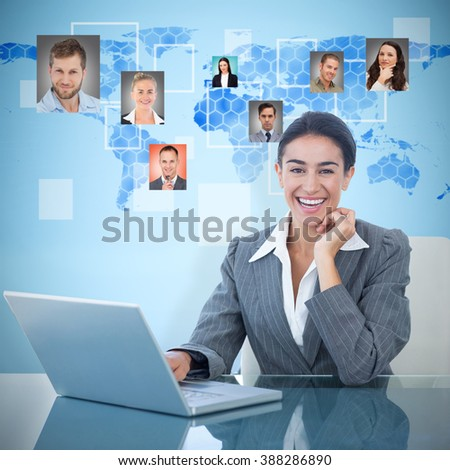 Cheerful businesswoman using laptop at desk against background with world map