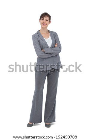 Cheerful businesswoman with arms crossed smiling at camera on white background  - stock photo