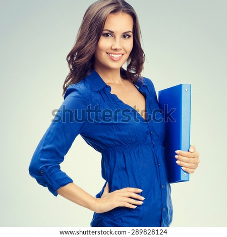 Cheerful businesswoman with blue folder, with blank copyspace area for slogan or text - stock photo