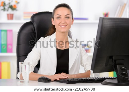 Cheerful businesswomen. Confident middle-aged businesswoman sitting at her working place - stock photo