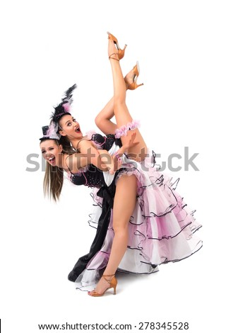 Cheerful cancan dancers posing wearing skirts, corsets and hats - stock photo