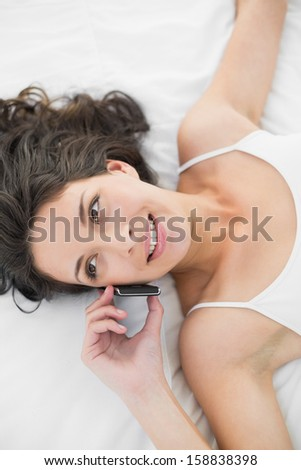 Cheerful casual brunette in white pajamas calling with her mobile phone in bright bedroom