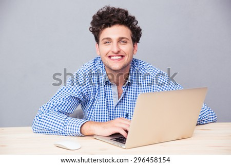 Cheerful casual man sitting at the table with laptop over gray background and looking at camera