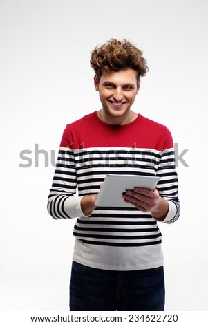 Cheerful casual man using tablet computer over gray background - stock photo