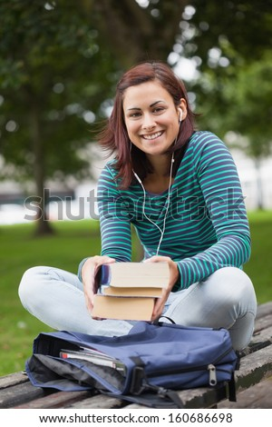 Cheerful casual student sitting on bench holding books on campus at college
