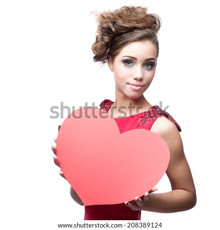 cheerful caucasian brunette young woman in red dress holding big red paper heart - stock photo