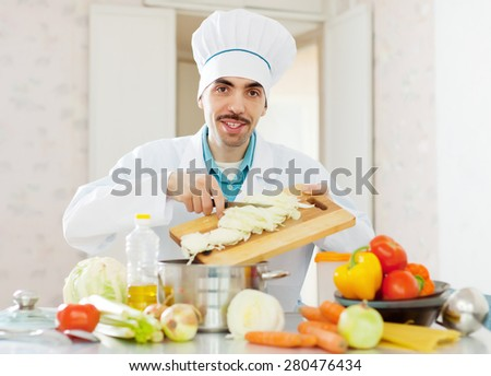 cheerful caucasian cook in white uniform does veggy lunch - stock photo