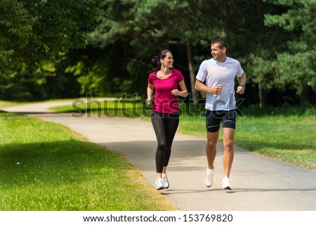 Cheerful Caucasian couple friends running in park - stock photo